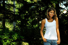 Attractive Young Biracial woman portrait. Portrait of young biracial woman in white tank top and jeans - next to tree stock photos
