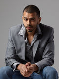Attractive young black guy in gray blazer isolated on gray backg Stock Photography