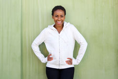 Attractive young black woman laughing against green wall Royalty Free Stock Photos