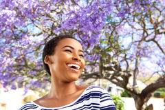Attractive young black woman laughing outdoors by flower tree Stock Photos