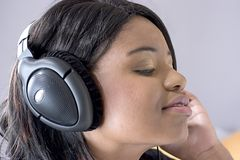 Attractive young black woman listening to music. On headphones Royalty Free Stock Images