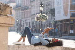 Attractive young black woman lying near the monument in the center of the city with the tablet in her hands. Woman Royalty Free Stock Image