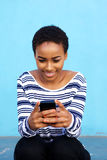 Attractive young black woman sitting with cell phone Stock Image