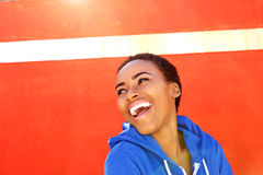 Attractive young black woman smiling against red wall Royalty Free Stock Images