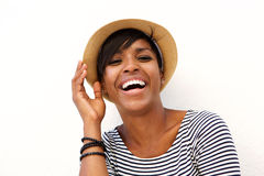 Attractive young black woman smiling with hat. Close up portrait of an attractive young black woman smiling with hat against white background Stock Photos
