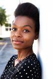 Attractive young black woman standing by a wall Royalty Free Stock Photography