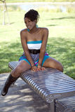 Attractive young black woman straddling park bench Royalty Free Stock Photos