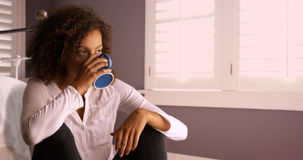 Attractive young black woman thinking and drinking from coffee cup. Stock Photography