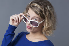 Attractive young blond blowing a kiss with sunglasses Stock Images
