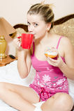 Attractive young blond charming woman sitting in pajamas on bed drinking beverage from red cup & biting color glace donut Stock Photography