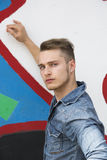Attractive young blond man against colorful graffiti wall Royalty Free Stock Photos
