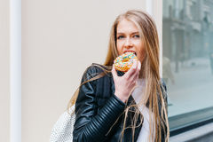 Attractive young blond sexy woman eating tasty colorful donut. Outdoors lifestyle portrait of pretty girl Stock Photo