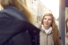 Attractive young blond woman chatting to a friend Royalty Free Stock Photography
