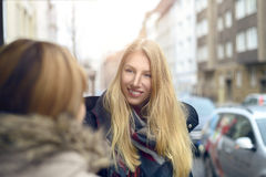 Attractive young blond woman chatting to a friend Stock Photo