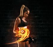 Attractive young blond woman doing bodybuilding. Holding fire dumbbells. Concept of hard work and motivation, dark brick wall background. Very high resolution stock photo