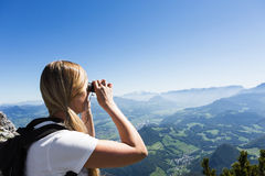 Woman in mountains. Attractive young blond woman hiker in the mountains taking a picture with a point and shoot camera ( or looking through binoculars ) at the Royalty Free Stock Photos