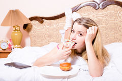 Attractive young blond woman lying in white bed biting color glace donut with tablet pc computer & looking at camera Stock Images