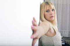 Attractive young blond woman posing on wall Royalty Free Stock Photos
