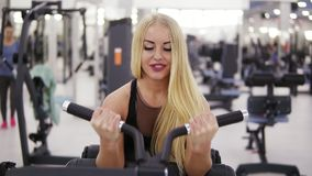 Attractive young blond woman with sporty body pumping up biceps muscles on training set in the gym. Doing excercises. Weightlifting. Healthy lifestyle concept stock footage