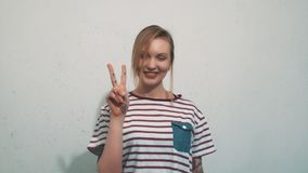 Attractive young blonde girl pull up two fingers in front of white wall stock video footage