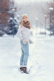 Attractive young blonde girl walking in winter forest. Pretty woman in wintertime outdoor. Wearing winter clothes. Knitted sweater Stock Photography