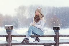 Attractive young blonde girl walking in winter forest. Pretty woman in wintertime outdoor. Wearing winter clothes. Knitted sweater Stock Photos