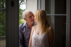 Attractive Young Blonde Kissing Her Senior Man near Opened Windows in the Room During Summer Time. Age Difference Royalty Free Stock Image