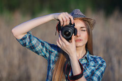 Attractive young blonde lady in blue plaid shirt straw hat enjoying her time taking photos on meadow hard noon sun. Attractive young blonde woman in blue plaid Royalty Free Stock Image