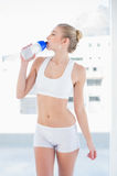 Attractive young blonde model drinking water in a bottle Royalty Free Stock Images