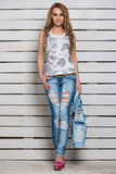 Attractive young blonde. Posing in blue ripped jeans and white flowered top Royalty Free Stock Photos