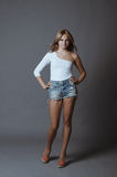 Attractive young blonde posing on grey. Young attractive seductive blonde in denim shorts standing against grey background Royalty Free Stock Photos