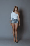 Attractive young blonde posing on grey. Young attractive seductive blonde in denim shorts standing against grey background Royalty Free Stock Images