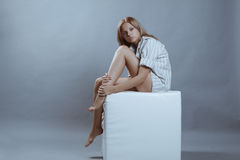 Attractive young blonde posing on grey. Young attractive seductive blonde in light striped shirt sitting on a white cube against grey background Stock Photo