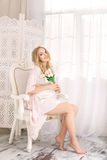 Attractive young blonde pregnant woman sitting on chair in white nightgown. Happy glamour sexy girl at home. Royalty Free Stock Images