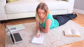 Attractive young blonde studying on her laptop