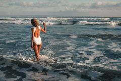 Attractive young blonde woman walking at beach stock photos
