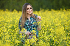 Attractive young blonde woman in blue plaid shirt straw hat enjoying her time on bright colorful blossoming yellow green meadow ha Royalty Free Stock Photos