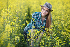 Attractive young blonde woman in blue plaid shirt straw hat enjoying her time on bright colorful blossoming yellow green meadow ha Stock Photos