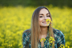 Attractive young blonde woman in blue plaid shirt straw hat enjoying her time on bright colorful blossoming yellow green meadow ha Royalty Free Stock Photography