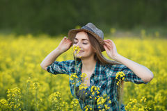 Attractive young blonde woman in blue plaid shirt straw hat enjoying her time on bright colorful blossoming yellow green meadow ha Royalty Free Stock Image