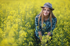 Attractive young blonde woman in blue plaid shirt straw hat enjoying her time on bright colorful blossoming yellow green meadow ha Stock Images