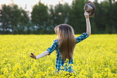 Attractive young blonde woman in blue plaid shirt straw hat enjoying her time on bright colorful blossoming yellow green meadow ha Stock Image