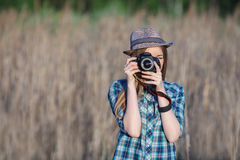 Attractive young blonde woman in blue plaid shirt straw hat enjoying her time taking photos on meadow outdoors Royalty Free Stock Photography