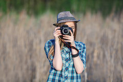 Attractive young blonde woman in blue plaid shirt straw hat enjoying her time taking photos on meadow outdoors Stock Photography