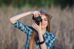 Attractive young blonde woman in blue plaid shirt straw hat enjoying her time taking photos on meadow outdoors Royalty Free Stock Photo