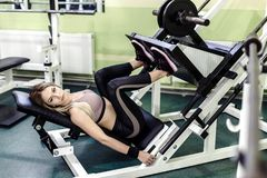 Attractive young blonde woman doing strength training on a gym. Pumping leg muscles Royalty Free Stock Photography