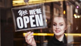 Attractive young blonde woman owner turns sign from close to open and shares a friendly, bright smile to camera. Inside