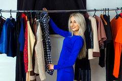 Attractive young blonde woman smiling and choosing clothes in st. Ore. Happy young lady with a lot of clothes. Shopping concept Stock Photos