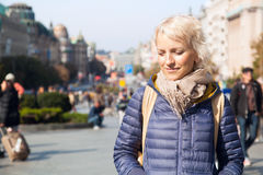 Attractive young blonde woman smiling. Young blonde woman in meditative mood at busy street in bright sunny day Stock Photo