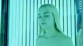 Attractive young blonde woman standing in tanning booth with her eyes closed. stock photography